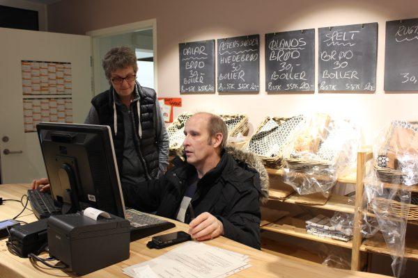Frivillige hjælper hinanden kasseapparatet i Vimby Høkeren.